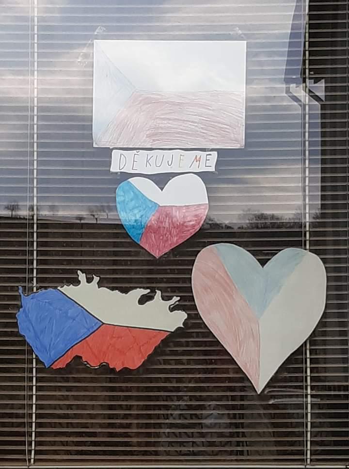 České vlajky vylepené v okně