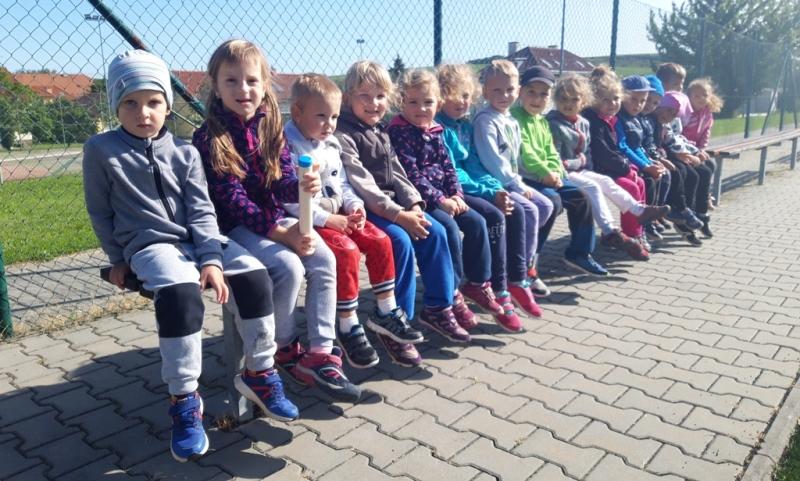 Děti sedí na lavičce a povzbuzují spolužáky