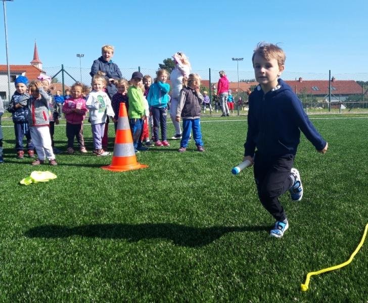 Chlapec běží se štafetou a spolužáci ho povzbuzují