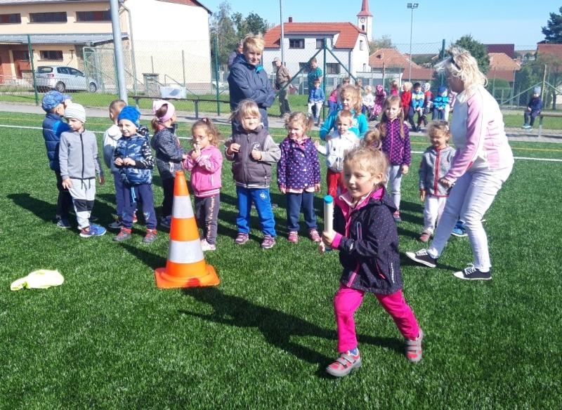 Dívka běží se štafetou a spolužáci ji povzbuzují