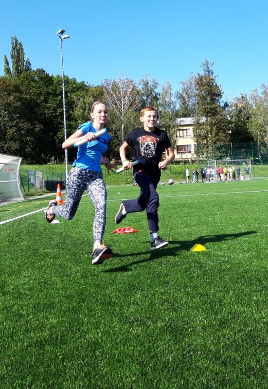 Žáci běží vedle sebe se štafetovými kolíky