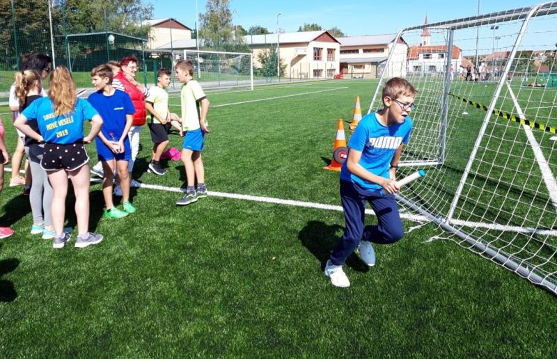 Chlapec běží se štafetou okolo fotbalové branky