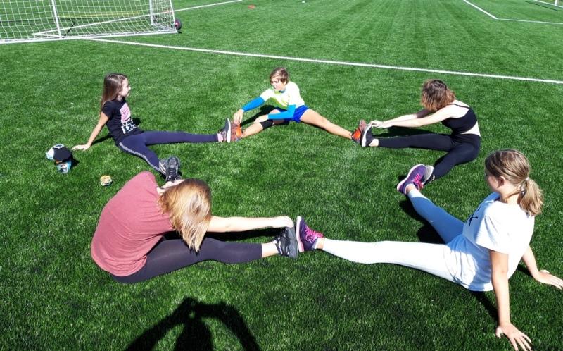 Děti se vsedě rozcvičují, přičemž nohama vytvořili hvězdici
