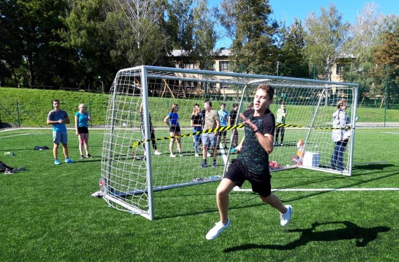 Chlapec běží se štafetou u fotbalové branky