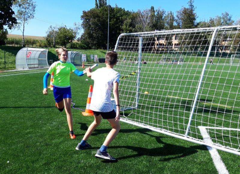 Žáci si předávají štafetu u fotbalové branky