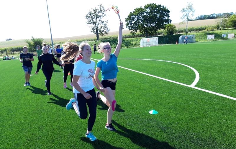 Žáci běží ve dvojicích po hřišti