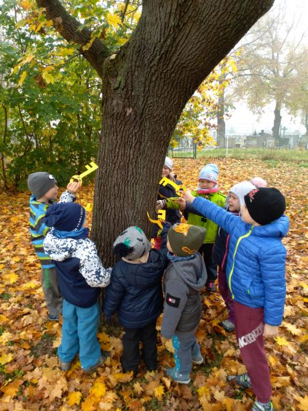 Kroužek dětí kolem stromu. Děti zamykají zahradu.