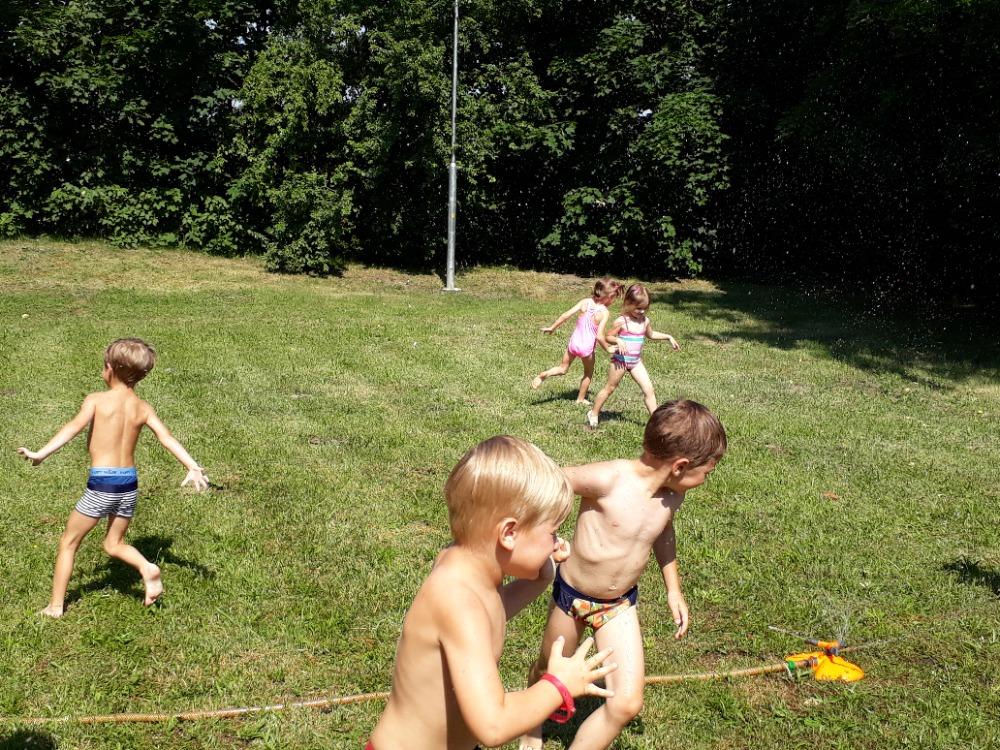 Děti běhají kolem vodotrysku