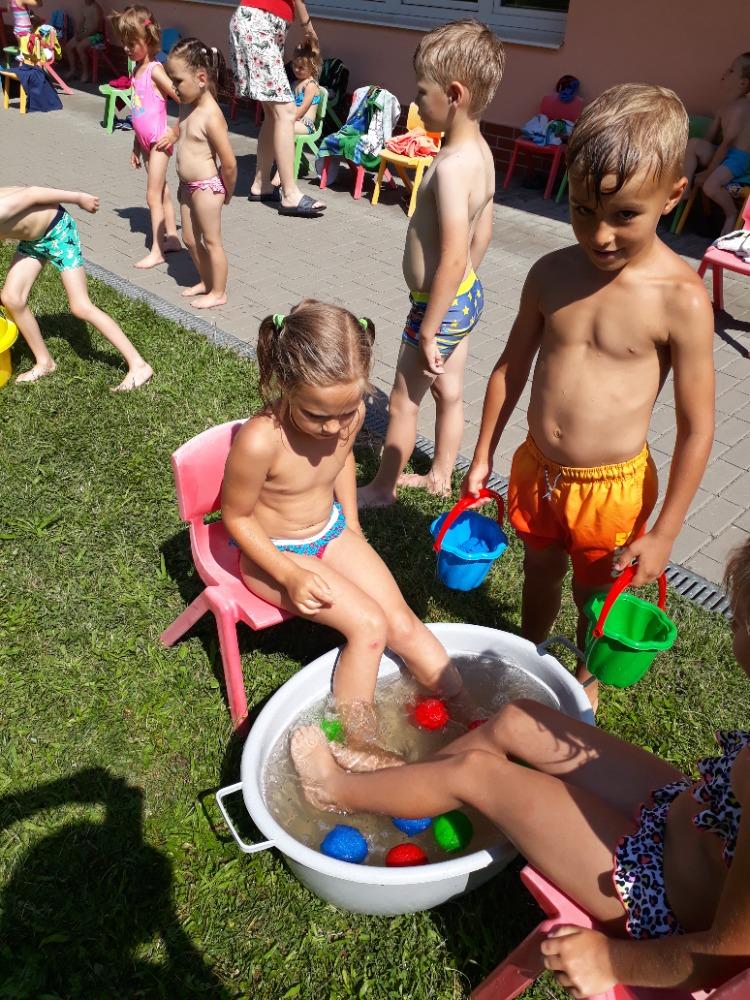 Děti loví nohama míčky z lavoru s vodou