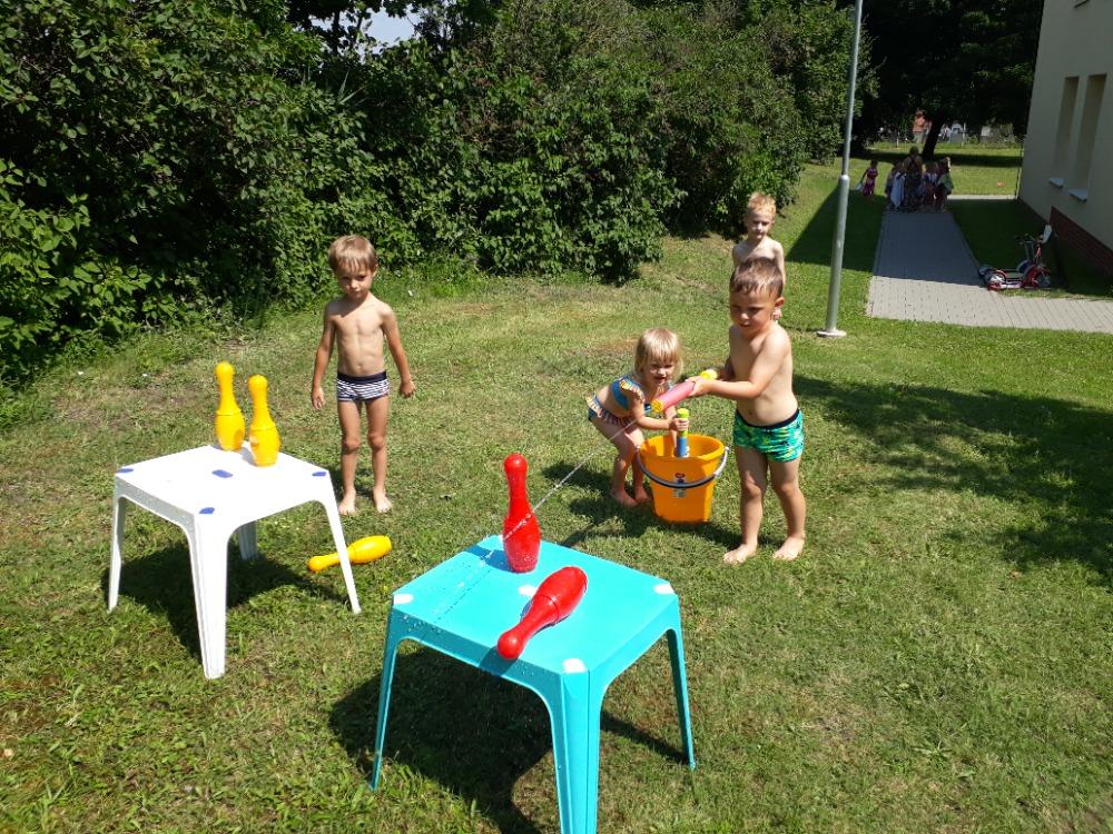 Děti srážejí kuželky vodní pistolí